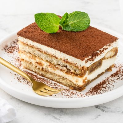 Traditional italian dessert tiramisu on a white plate on a marbl