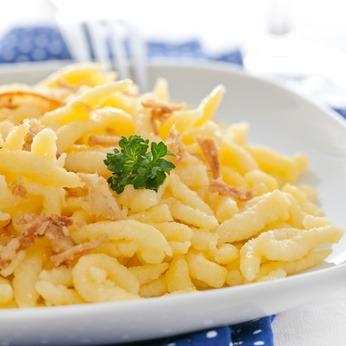 frische Spätzle mit Röstzwiebeln auf Teller / fresh spaetzle with fried onions on plate