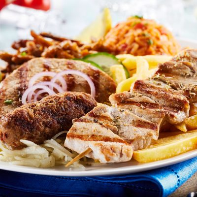 Mixed Greek grill platter with gyros, souvlaki and spicy pork skewers served with potato chips and tomato rice pilaf in a close up view